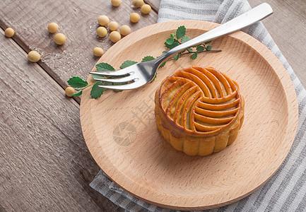 中秋传统美食月饼摆拍木板背景图片