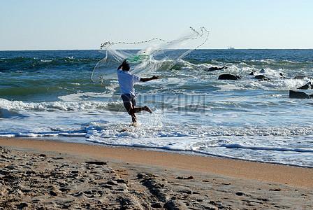 海边撒网的男人图片
