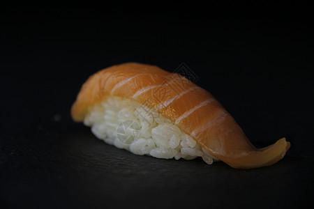 放在黑石板上的三文鱼手握寿司图片