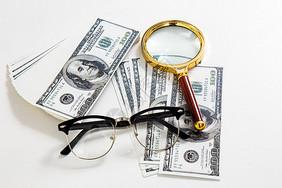 桌面上摆放着钞票和放大镜图片