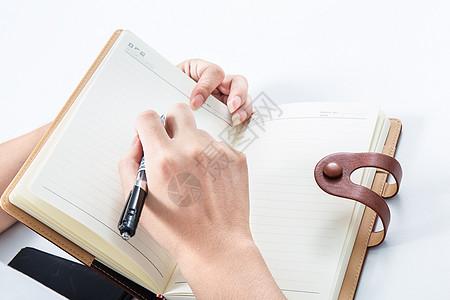 手持笔在本子上书写内容图片