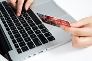 手持信用卡在笔记本前敲击图片