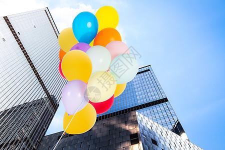 蓝天下聚集在一起的彩色气球图片