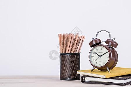 桌子上的铅笔闹钟书本图片