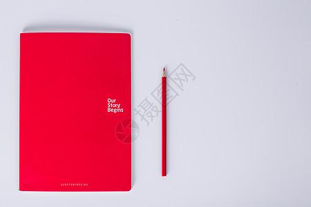白色背景下红本子和红色铅笔摆拍图片
