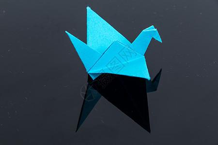 蓝色千纸鹤黑色背景反光图片