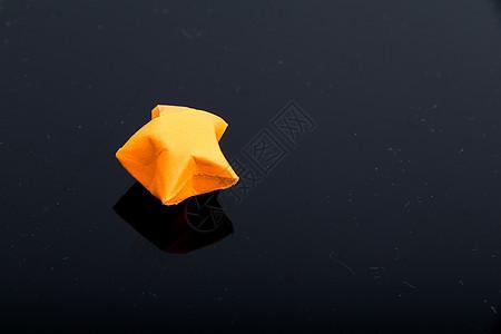 黑色背景橙色纸质星星图片