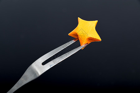 橙色纸质星星黑色背景叉子图片