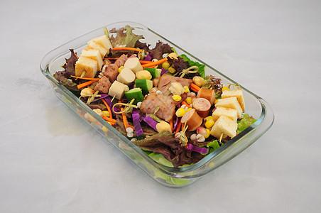 白背景玻璃碗里的培根香肠面包蔬菜沙拉图片