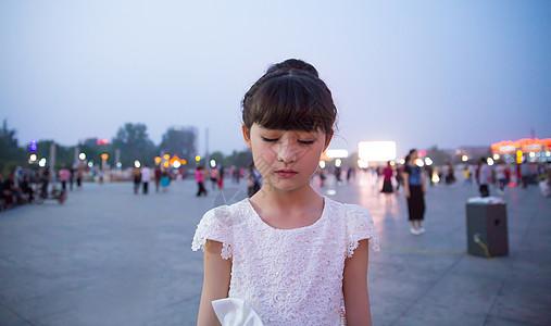 傍晚小女孩穿着白裙站在广场上闭着眼睛图片