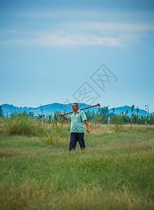 清晨农夫在山下田地草地劳动图片