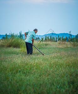 清晨农夫扛着锄头在山下开荒种植图片