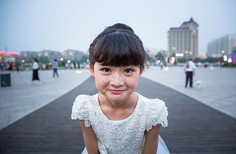 傍晚小姑娘穿着白裙站在广场上露出特殊的表情图片