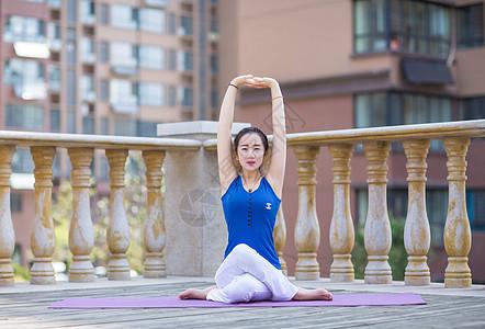 清晨穿着白裤子蓝背心在阳台上做瑜伽的年轻女孩图片