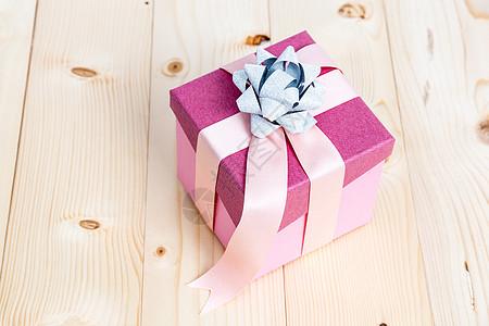 木制背景粉色缎带礼物盒图片