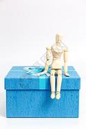 蓝色礼物盒与木制人偶图片