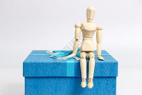 蓝色礼物盒与坐着的人偶图片