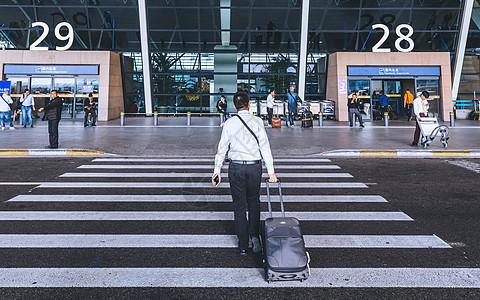 拉着行李走向机场的男子图片