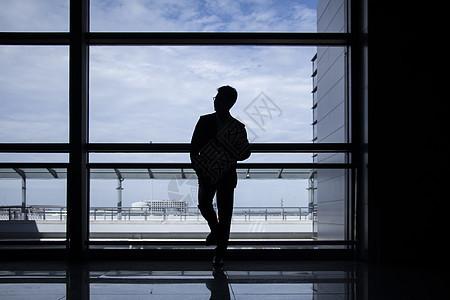 商务人士站在机场落地窗前图片