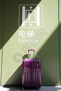 电梯标志下的行李箱图片