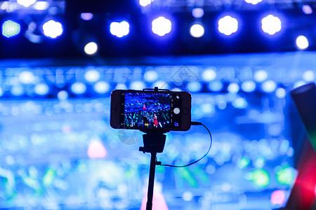 用自拍杆架着手机 录制演出视频图片