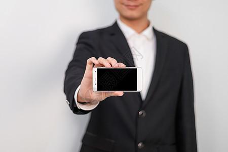 商务人士拿着手机特写虚化图片