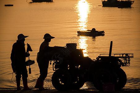 日出海边渔民捕鱼照图片