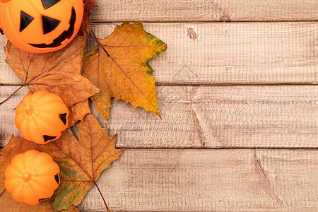 万圣节可爱卡通南瓜灯秋叶木质板背景素材图片