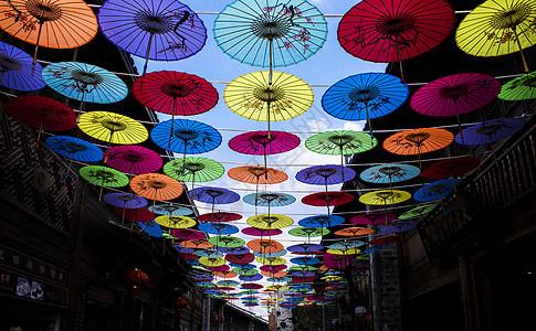 仰望漂浮在晴朗天空中五颜六色的伞图片