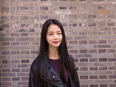 文艺美女微笑灰墙前拍摄图片