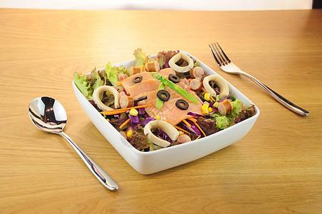木桌上美味诱人的鸡肉鱿鱼芦笋生菜甘蓝火腿黑水榄沙拉图片
