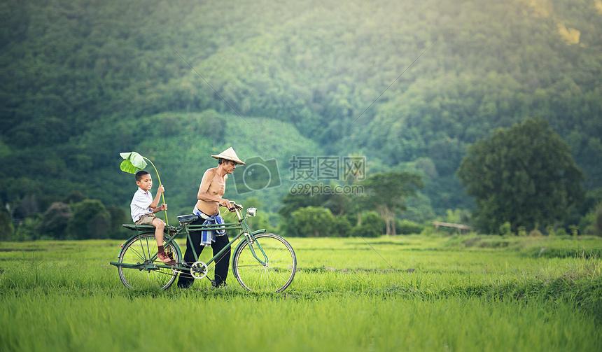 田园中父亲自行车推着孩子图片