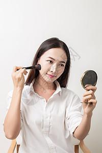 美丽女性手拿粉刷镜子化妆 图片