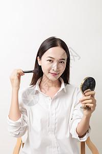 美丽女性手拿粉刷镜子化妆图片