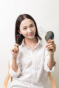 美丽女性手拿粉刷镜子展示图片
