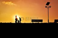 夕阳下公园里的幸福一家三口图片