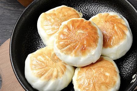 刚出锅的金黄色上海生煎包鲜嫩多汁图片