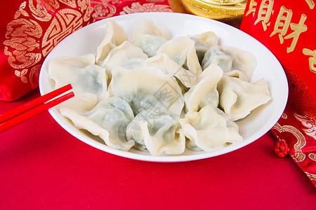 新春过年冬至红色背景上的一盘饺子图片