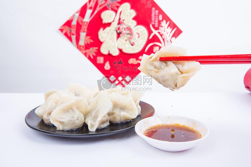 福字为背景的人夹饺子吃的冬至新春节日图片