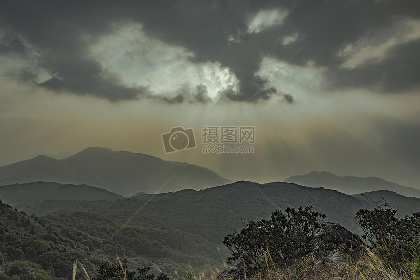 透过云层照射高山的阳光图片