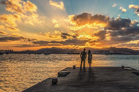 夕阳下母子牵手漫步于海边图片