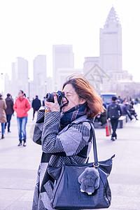 城市街头女性摄影师在拍照图片