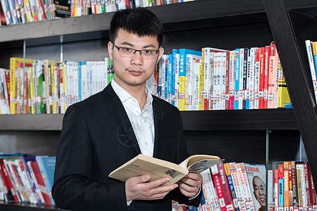 书架前看书的商务人士男士图片