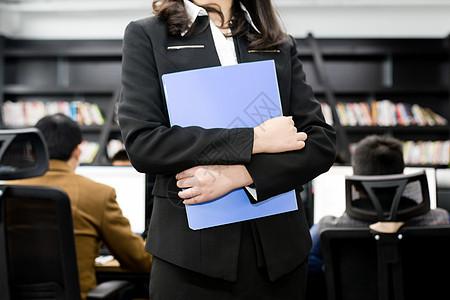 抱着文件夹的职业女性图片