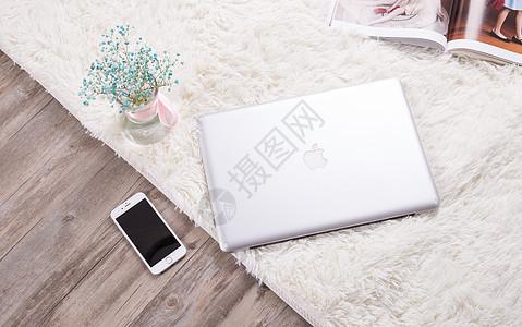 生活地毯上放着电脑和手机图片
