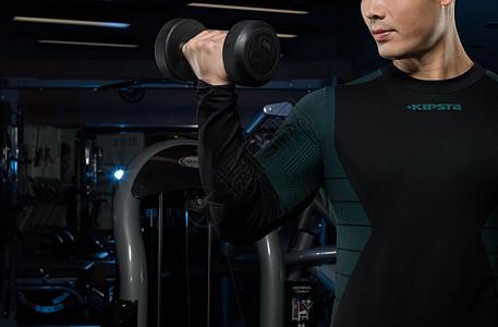 健身教练手拿哑铃动作展示图片