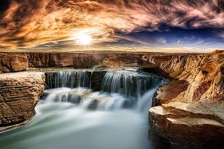 阳光下岩石边的瀑布图片