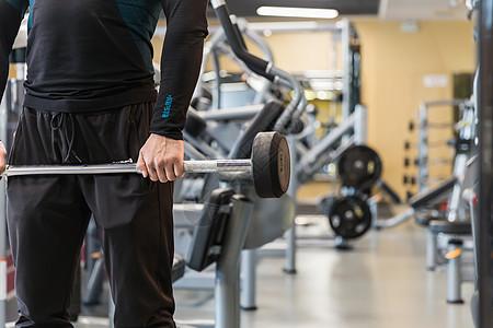 健身房强壮男人拿杠铃特写图片