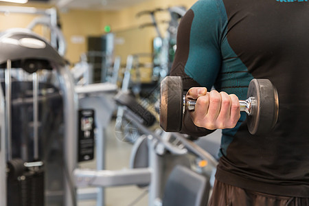 健身房强壮男人拿哑铃特写图片