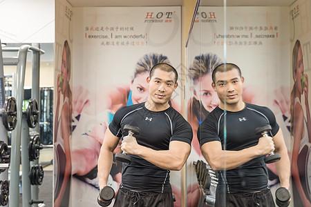 健身房强壮男人哑铃训练图片